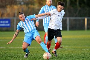 Adam Hunt battles with an AFC Uckfield Town player for the ball